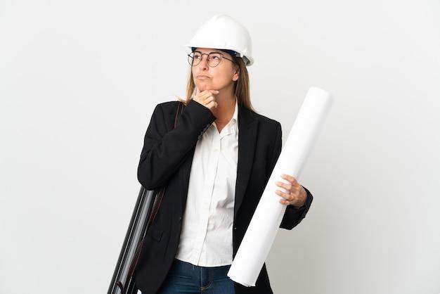 헬멧과 의구심을 갖는 고립 된 벽에 청사진을 들고 중년 건축가 여자
