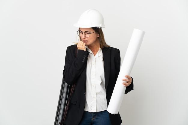 Женщина-архитектор среднего возраста в шлеме и держит чертежи над изолированной стеной, сомневаясь