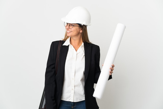 헬멧과 격리 된 벽에 청사진을 들고 중년 건축가 여자 측면을보고 웃