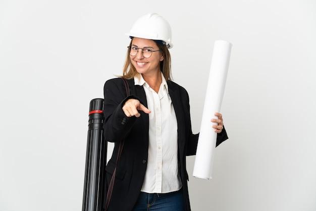 헬멧과 행복 한 표정으로 앞을 가리키는 격리 된 벽 위에 청사진을 들고 중년 건축가 여자