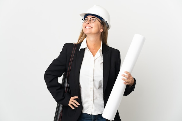 헬멧과 격리 된 벽에 청사진을 들고 중년 건축가 여자 엉덩이에 팔을 포즈와 미소