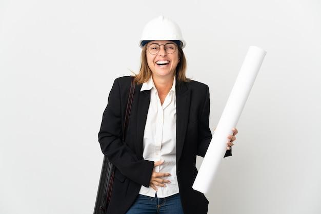 헬멧과 격리 된 벽에 청사진을 들고 중년 건축가 여자 많이 웃고