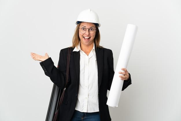 헬멧과 충격 된 표정으로 격리 된 벽 위에 청사진을 들고 중년 건축가 여자