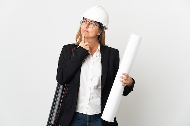 Middle age architect woman with helmet and holding blueprints over isolated having doubts while looking up