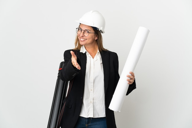 Middle age architect woman with helmet and holding blueprints over isolated wall shaking hands for closing a good deal