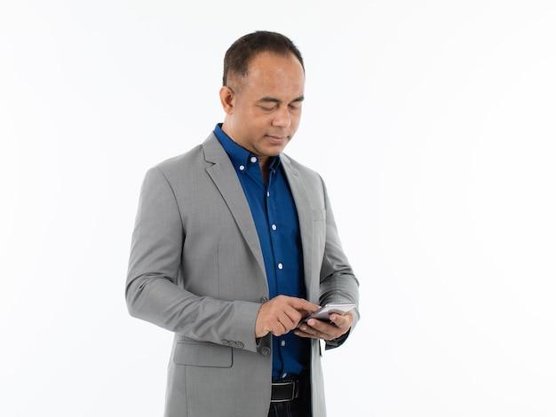 カジュアルなスタイルのグレーのジャケットを着て、スマートフォンを手に持って、集中力と小さな笑顔で電話を探している中年のアジア人男性。白い背景で隔離