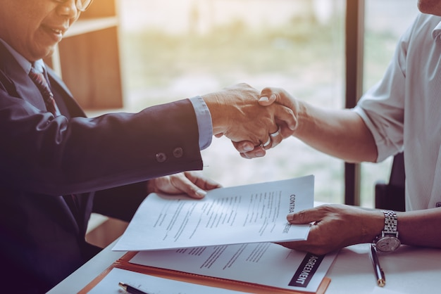 Адвокаты юристов-партнеров среднего возраста пожимают друг другу руки после обсуждения заключенного контракта.