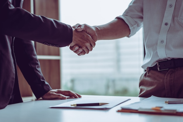 Middle age asian partner lawyers attorneys shaking hands after discussing a contract agreement done.
