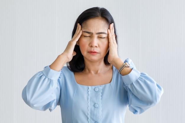 중년 아시아 여성은 고통을 느끼고 갑작스러운 두통과 뇌졸증 발작을 일으키며 고통받는 얼굴로 머리를 잡고 있습니다. 두뇌와 머리 문제의 개념입니다.