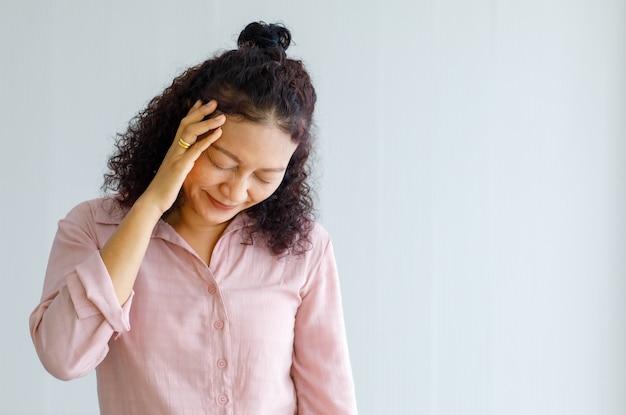 중년 아시아 여성은 고통을 느끼고 갑작스러운 뇌졸중 발작을 일으키며 고통받는 얼굴로 머리를 잡고 있습니다. 두뇌와 머리 문제의 개념입니다.