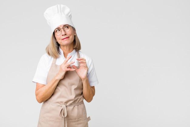 Женщина-пекарь среднего возраста чувствует себя гордой, озорной и высокомерной, замышляя злой план или думая о хитрости против плоской стены