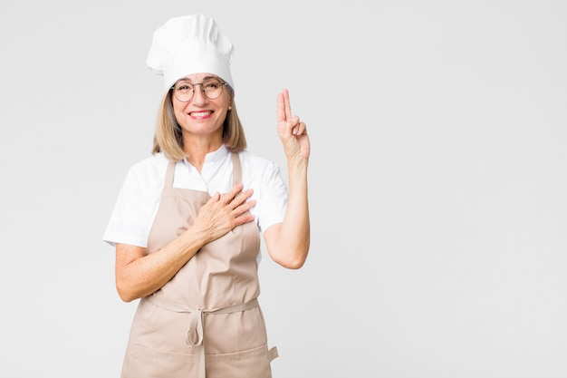 Middle age baker woman looking happy, confident and trustworthy, smiling and showing victory sign, with a positive attitude against flat wall