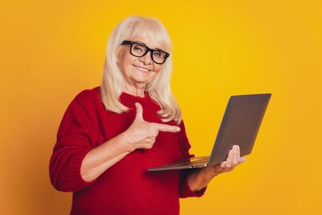 Красивая блондинка деловая женщина среднего возраста, работающая с ноутбуком на желтом фоне