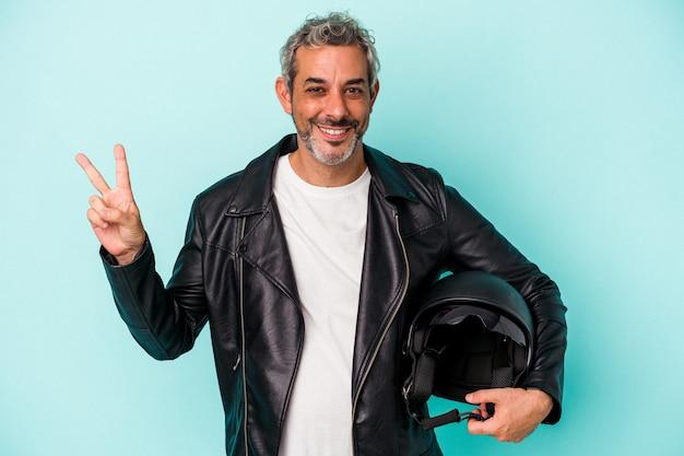 青い背景に分離されたヘルメットを持っている中年のバイカー白人男性は、指で平和のシンボルを示して楽しくてのんきです。