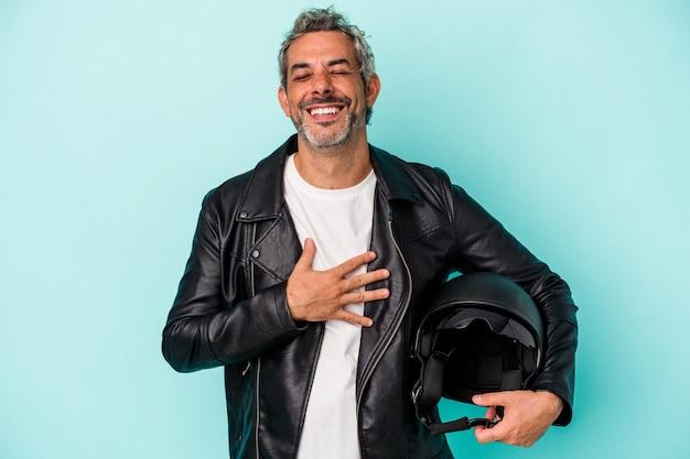 青い背景で隔離のヘルメットを保持している中年のバイカー白人男性は、胸に手を置いて大声で笑います。