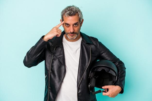 Байкер среднего возраста кавказский человек, держащий шлем, изолированный на синем фоне, указывая висок пальцем, думая, сосредоточился на задаче.