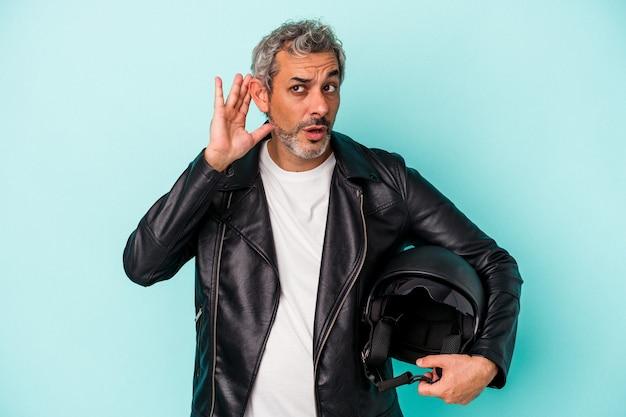 Байкер среднего возраста кавказский мужчина держит шлем, изолированные на синем фоне, пытаясь слушать сплетни.