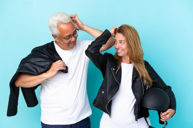 Байкеры среднего возраста пара с мотоциклетным шлемом, изолированные на синем фоне, сомневаясь, почесывая голову