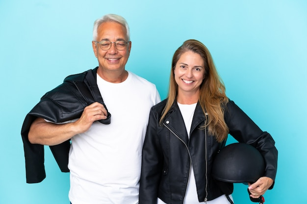 Байкеры среднего возраста пара в мотоциклетном шлеме, изолированные на синем фоне, позирует с руками на бедрах и улыбается