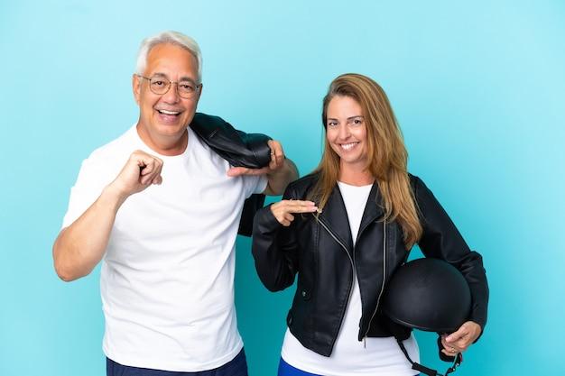 Байкеры среднего возраста пара с мотоциклетным шлемом, изолированные на синем фоне, гордые и самодовольные в любви к себе концепции