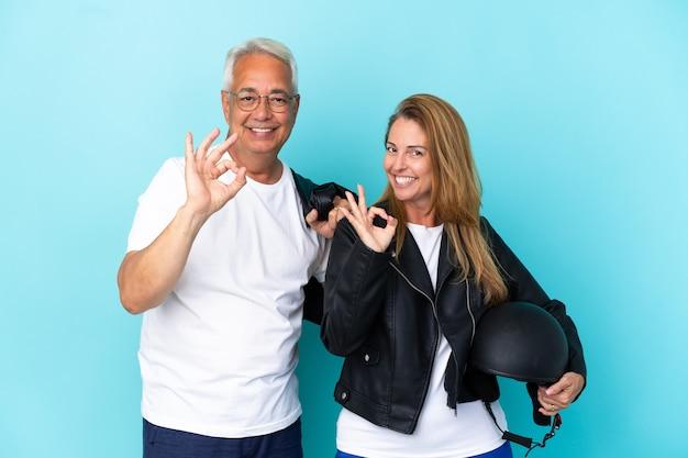 Байкеры среднего возраста пара в мотоциклетном шлеме, изолированные на синем фоне, показывая пальцами знак ок