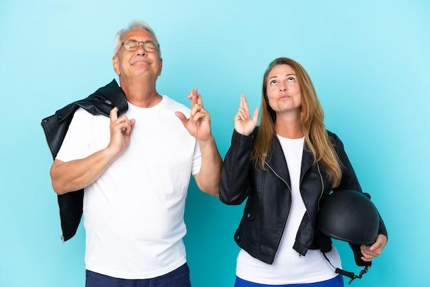 Байкеры среднего возраста пара с мотоциклетным шлемом на синем фоне со скрещенными пальцами и желанием всего наилучшего