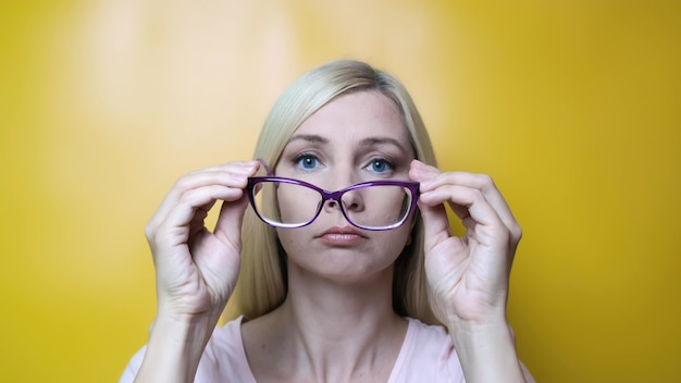 A middle age blond woman putting on stylish fashionable glasses and smiling, myopia, astigmatism and ophthalmologic diseases.