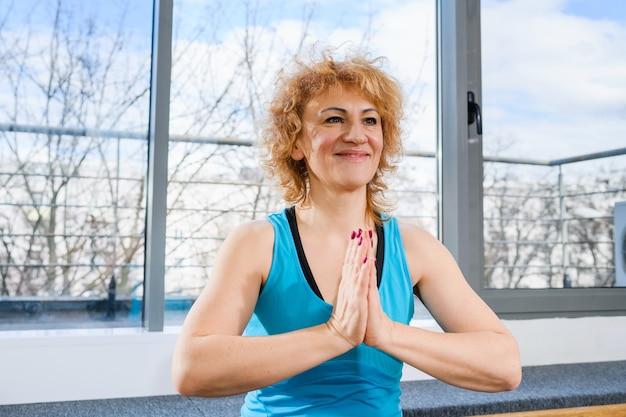 Блондинка среднего возраста сидит в позе лотоса йоги с руками в жесте намасте на спортивном коврике