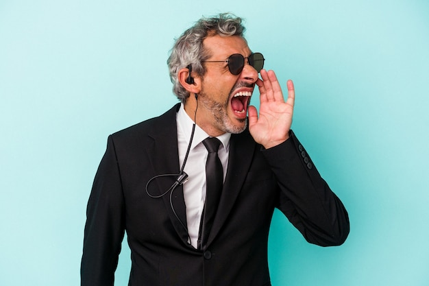Middle age bodyguard caucasian man isolated on blue background  shouting and holding palm near opened mouth.