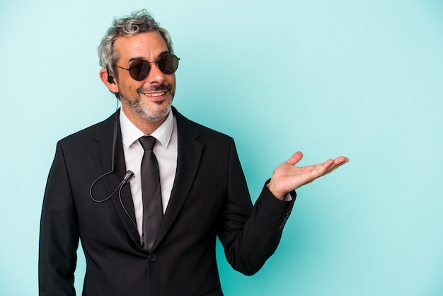 Middle age bodyguard caucasian man isolated on blue background  showing a copy space on a palm and holding another hand on waist.