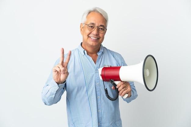 Бразильский мужчина среднего возраста изолирован, держит мегафон и улыбается и показывает знак победы