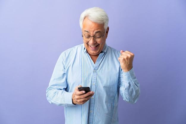 紫色の背景に分離された中年のブラジル人男性は驚いてメッセージを送信します