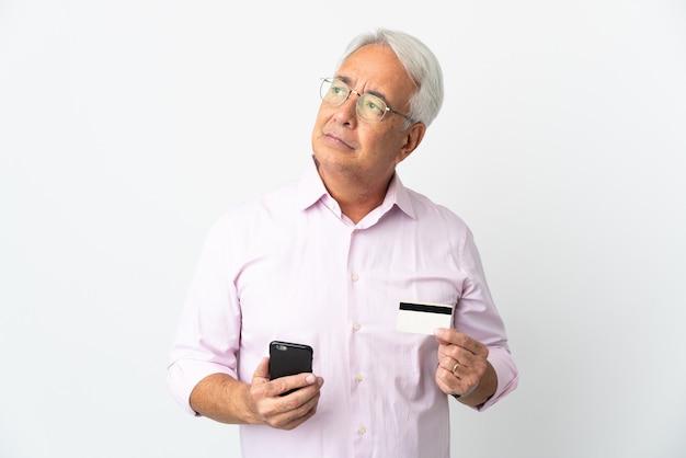 흰색 배경에 격리된 중년 브라질 남성은 생각하는 동안 신용카드로 모바일 구매
