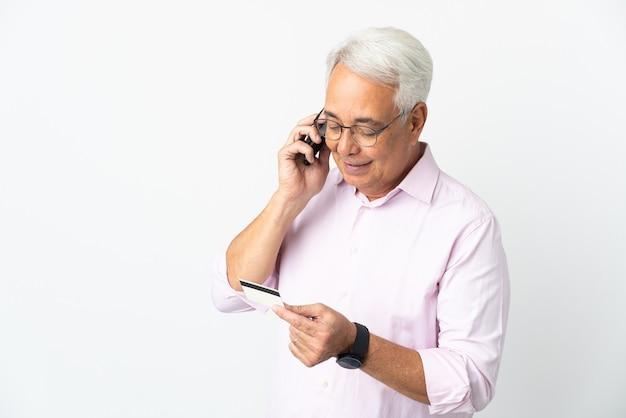 クレジットカードで携帯電話で購入する白い背景で孤立した中年のブラジル人男性
