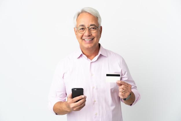 신용 카드로 모바일로 구매하는 흰색 배경에 고립 된 중년 브라질 남자