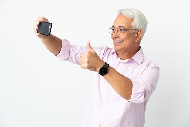 携帯電話でselfieを作る白い背景で隔離中年ブラジル人男性