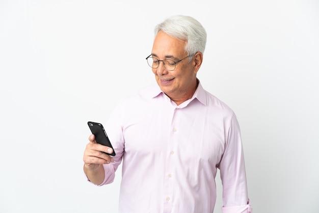 携帯電話でメッセージやメールを送信する白い背景で隔離中年ブラジル人男性