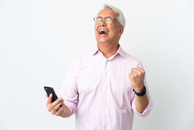 Бразильский мужчина среднего возраста изолирован на белом фоне с помощью мобильного телефона и делает жест победы