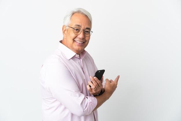 Бразильский мужчина среднего возраста, изолированные на белом фоне, используя мобильный телефон и указывая назад