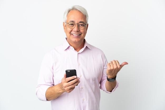 Бразильский мужчина среднего возраста, изолированные на белом фоне с помощью мобильного телефона и указывая на боковой
