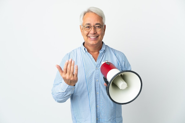 Middle age brazilian man isolated on white background holding a megaphone and inviting to come with hand