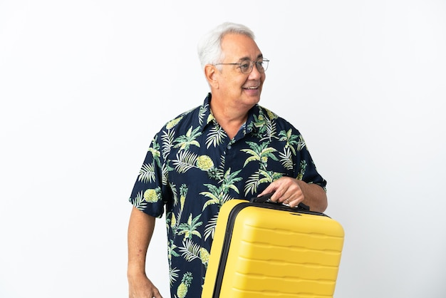 Middle age brazilian man isolated on white background in vacation with travel suitcase