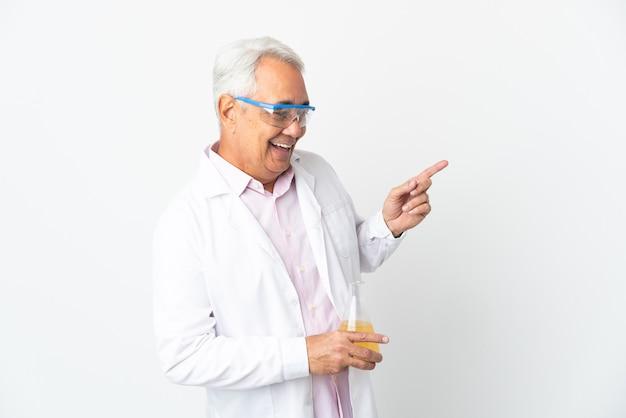 중간 나이 브라질 과학 남자 과학 측면에 손가락을 가리키고 제품을 제시하는 흰색 배경에 고립