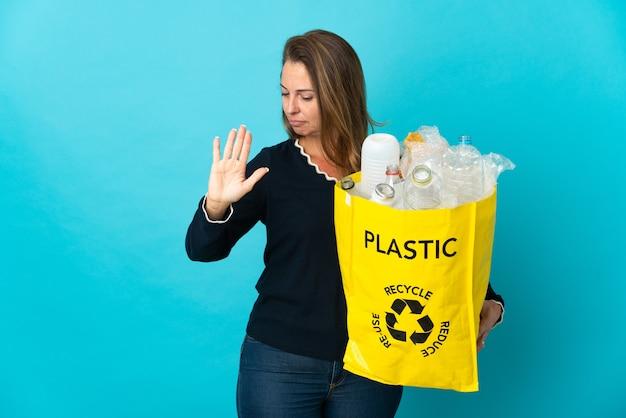 青い壁でリサイクルするためにペットボトルでいっぱいのバッグを持っている中年のブラジル人女性は、停止ジェスチャーをして失望しました
