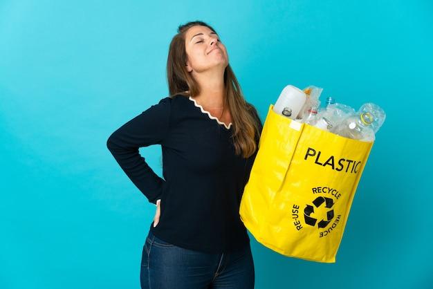 플라스틱 병으로 가득 찬 가방을 들고 중년 브라질 여자