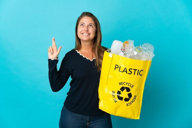 ペットボトルでいっぱいのバッグを持っている中年のブラジル人女性