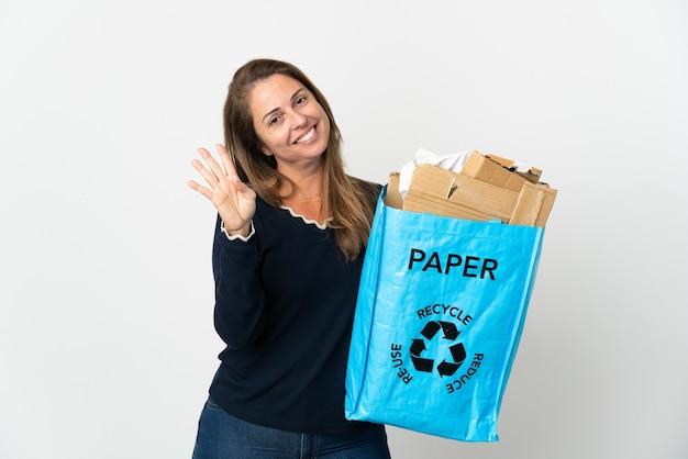 幸せな孤立した背景の上にリサイクルするために紙でいっぱいのリサイクルバッグを持って、指で4を数える中年のブラジル人女性