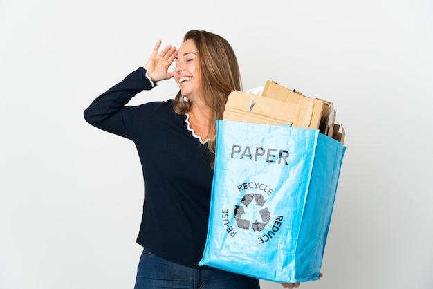 たくさんの笑顔で孤立した背景の上にリサイクルするために紙でいっぱいのリサイクルバッグを保持している中年のブラジル人女性