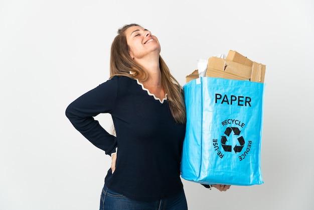 노력을 한 데 대한 요통으로 고통받는 고립 된 벽 위에 재활용 종이로 가득 찬 재활용 가방을 들고 중년 브라질 여자