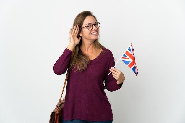 귀에 손을 넣어 뭔가를 듣고 흰색 배경에 고립 된 영국 국기를 들고 중년 브라질 여자